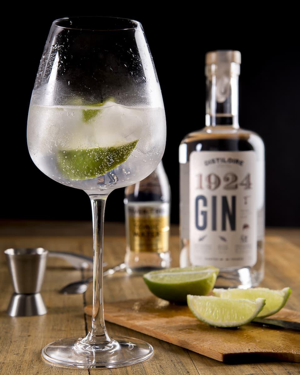 verre de gin tonic avec rondelles de citron et bouteille de gin
